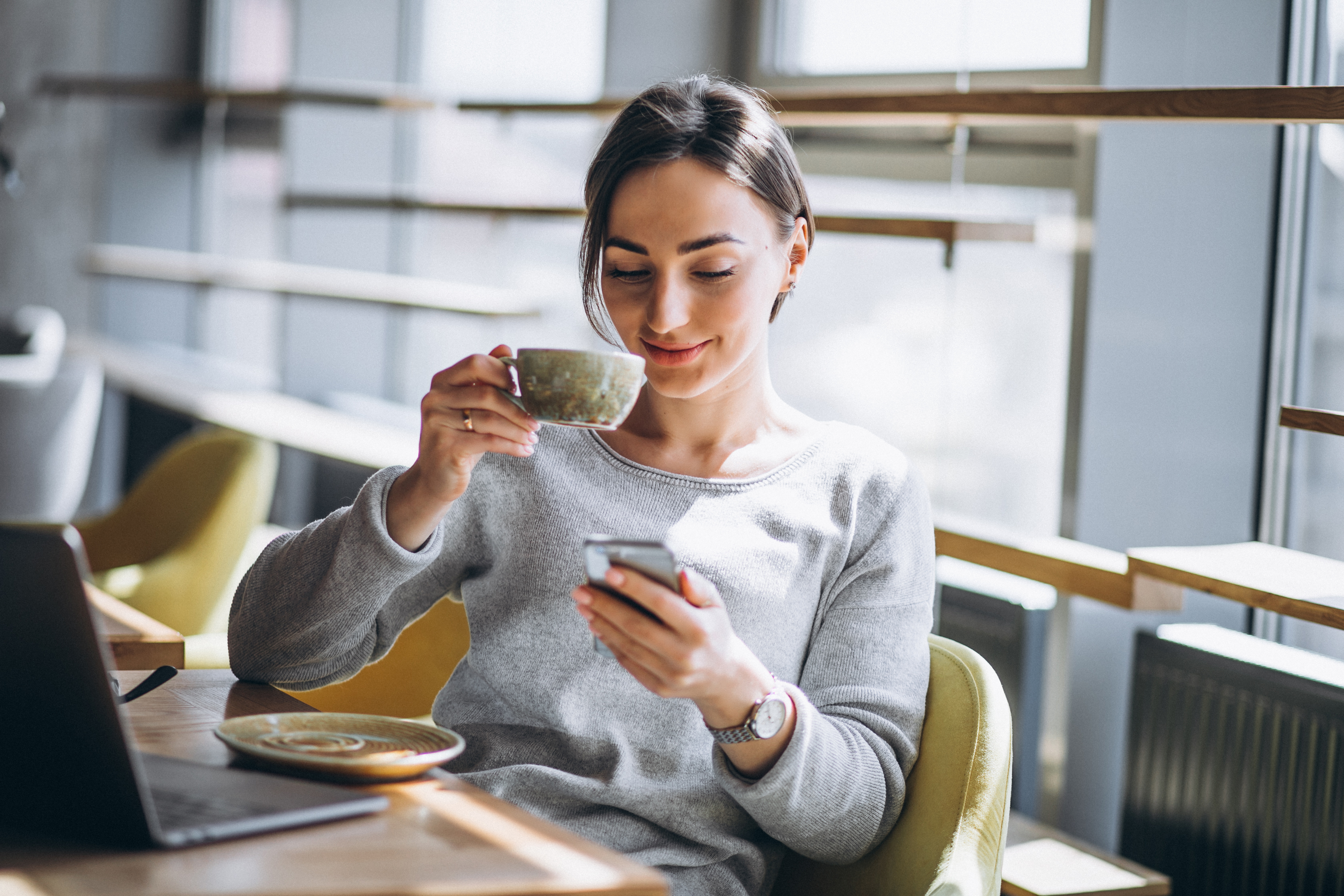 A woman smiling at her phone while drinking a cup of coffee