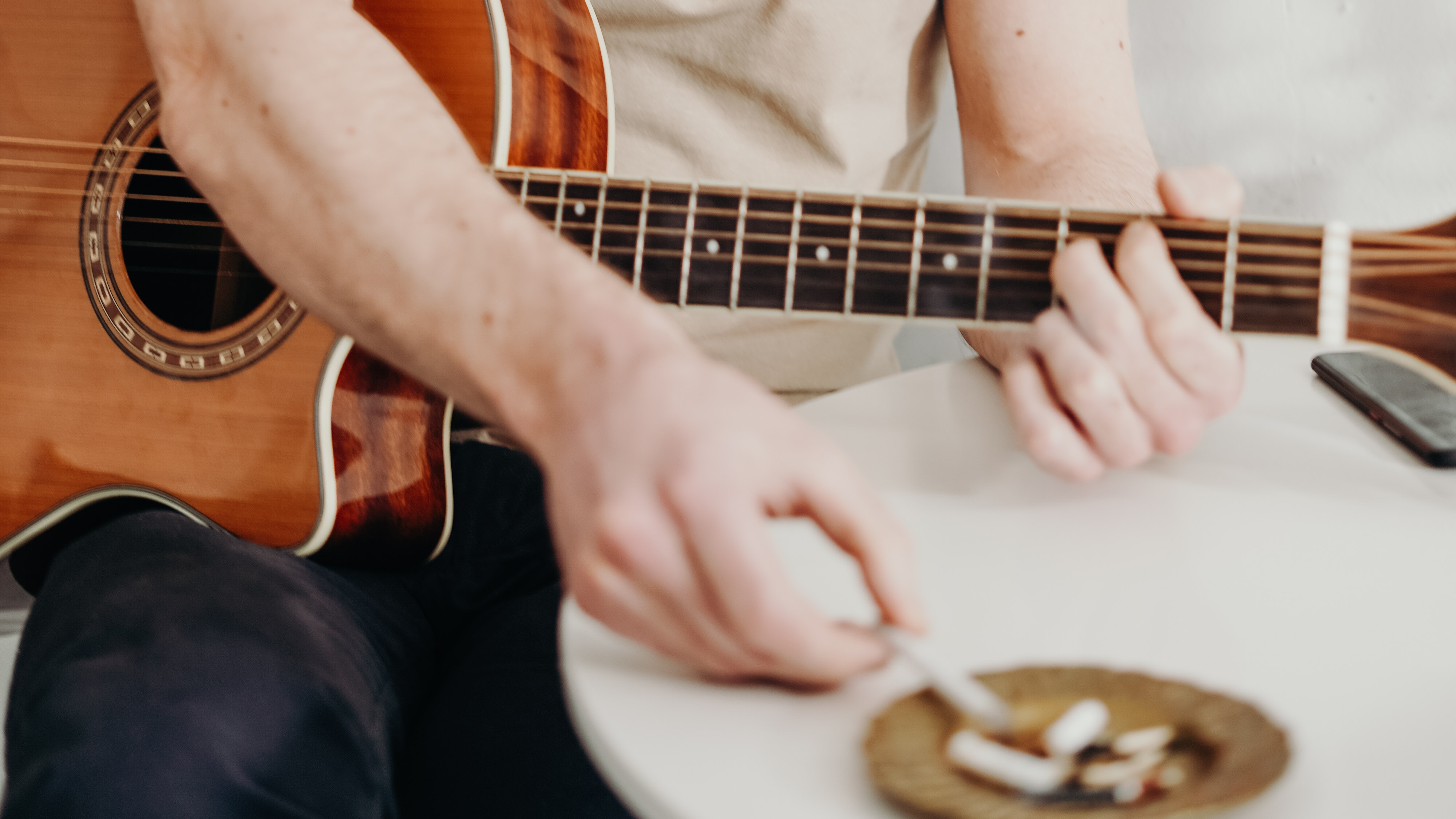 A man holding a guitar and a cigarette