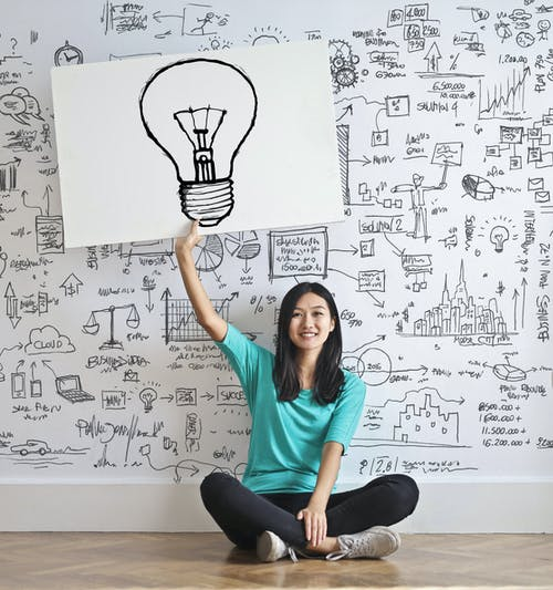 A woman holding a poster with a lightbulb above her head