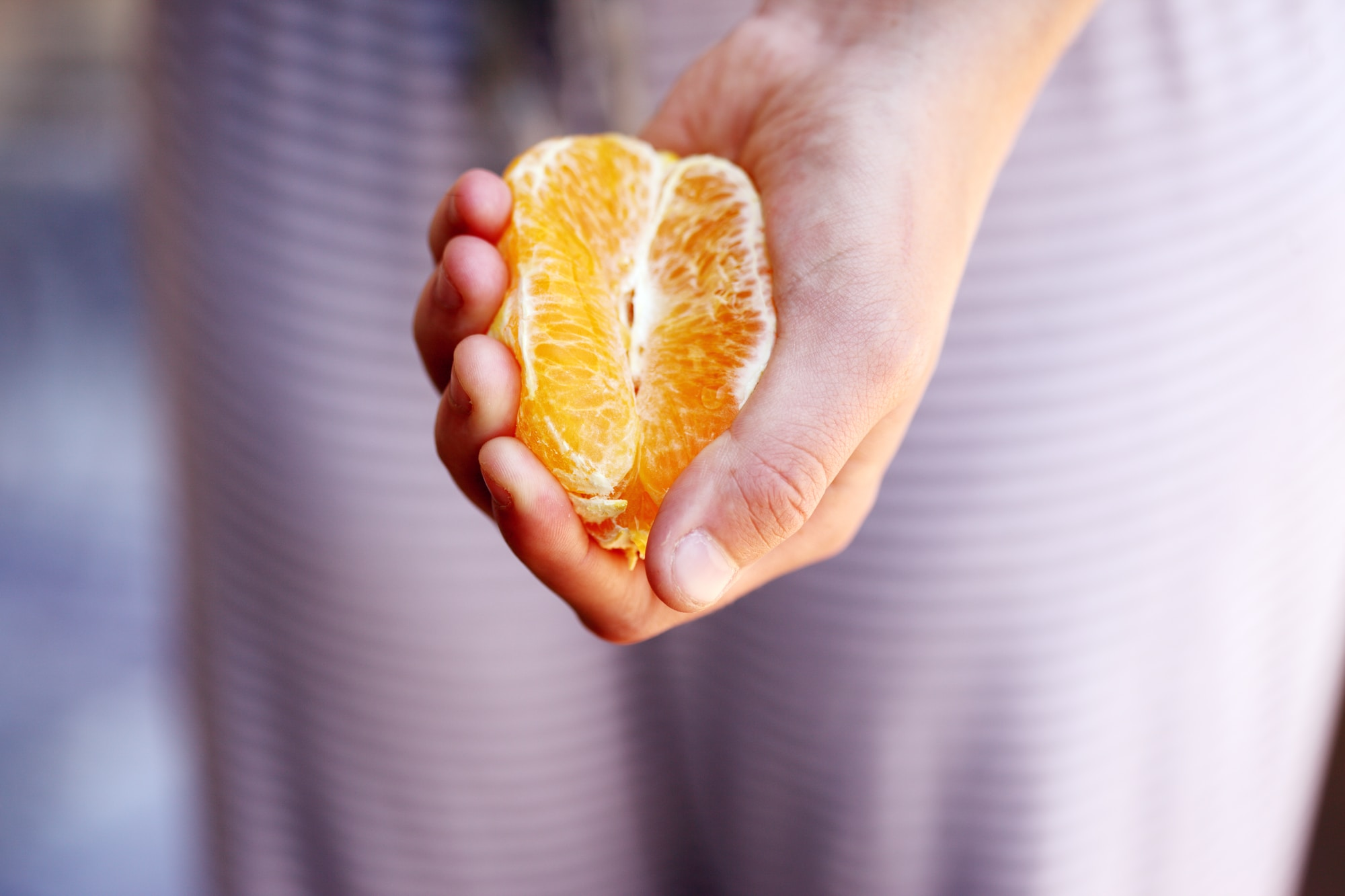 Woman squeezing a fresh, juicy orange. Unporn image collection.